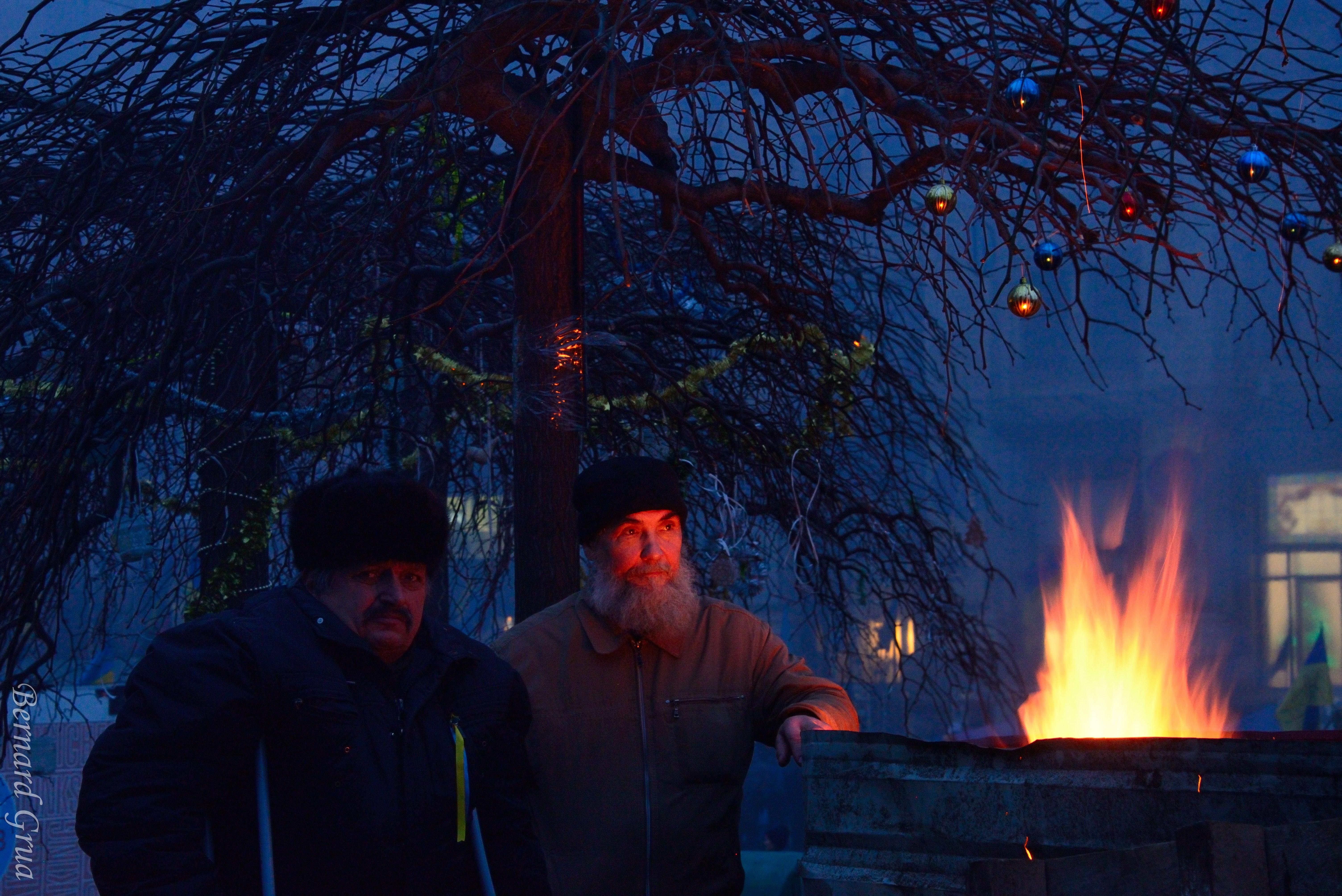 """Maïdan, Kyiv, 31/12/2013, photo Bernard Grua DR Commentaire de Pavlo Kuzyk, ami ukrainien: """"Une autre de mes photos préférées. Le feu fournit un bel éclairage et des reflets sur les décorations du Nouvel An, et les visages des hommes reflètent leur inquiétude et leur incertitude quant à l'avenir du pays."""""""