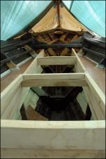 """Hiloire avant et étrave (non encore pontée) Le pont est du contreplaqué posé sur les barrots, recouvert d'époxy (résine) et d'un film de """"roving"""" (tissu de verre). Lebateau est rcouvert, provisoirement, de bâches s'appuyant sur le mat et la vergue posées en longueur ainsi que sur des bambous passés dans les chandeliers. les bâches sont décolées du mat et de la vergue, vernis, par des arseaux de polystyrène. Pont-Aven, Finistère, Bretagne 28/07/2016"""