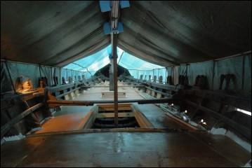 """Pont, hiloire arrière, hiloire centrale, pied de mat hiloire avant. Le pont est du contreplaqué posé sur les barrots, recouvert d'époxy (résine) et d'un film de """"roving"""" (tissu de verre). Lebateau est rcouvert, provisoirement, de bâches s'appuyant sur le mat et la vergue posées en longueur ainsi que sur des bambous passés dans les chandeliers. les bâches sont décolées du mat et de la vergue, vernis, par des arseaux de polystyrène. Pont-Aven, Finistère, Bretagne 28/07/2016"""
