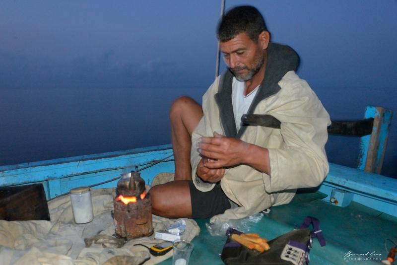 """Il est 5:30 du matin ce vendredi 30/09/2016. Le pêcheur kerkennien Fathi Djebel d'El Attaya est en route depuis plus d'une heure sur sa felouque à moteur """"in bord"""". Dès le départ, son premier geste a été d'alumer son canoun avec du charbon de bois sur lequel il préparera en permance un thé très sucré. Dans une heure et demi, il sera sur les lieux où il a mouillé ses centaines de """"drinas"""" (nasses) pour piéger le poulpe. Le ciel est constellé d'étoile mais une brume basse mouille le bateau. Fathi n'a pas de carte, pas de compas de route. Pour l'instant il fait cap plein Est. Il retrouvera ses pièges grace à un petit GPS de voiture. Son diesel le propulse à une vitesse de ... 8 km/h. Quatorze ans ont passé. Les magnifiques felouqes ne glissent plus en silence sous leurs élégantes voiles latines. A Kerkennah, un des ultimes sanctuaires de la voile au travail est fracassé. Pour l'instant les charpentiers navals tels continuent à construire des merveilles. Pour combien de temps?"""