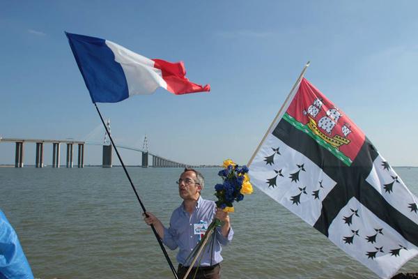 """Bernard Grua avec les couleurs ukrainiennes, les drapeaux français et nantais, devant le pont St Nazaire-St Brévin. Manifestation """"No Mistrals for Putin"""""""